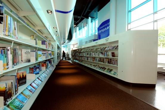 Bookshelves, books, signage and large windows to allow good daylight in the library space