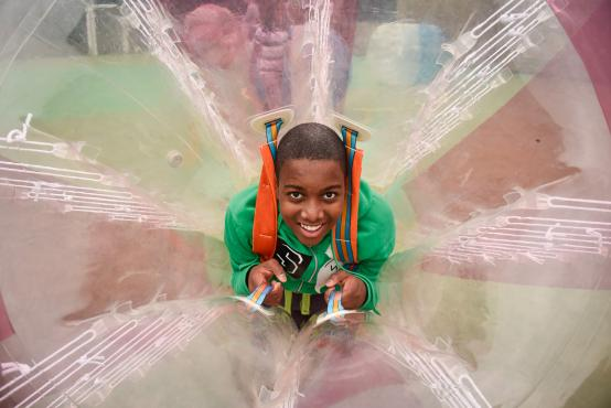 Young man smiling inside some plastic play apparatus
