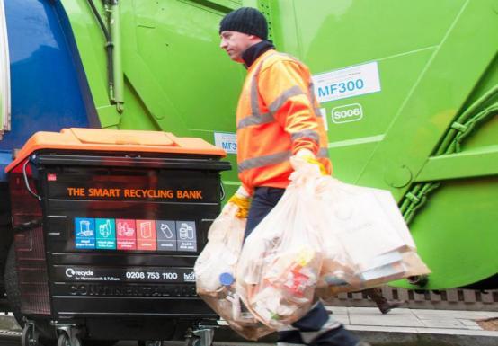 Bin man carrying rubbish and recycling bags