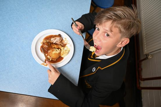 Schoolboy eating a meal at school