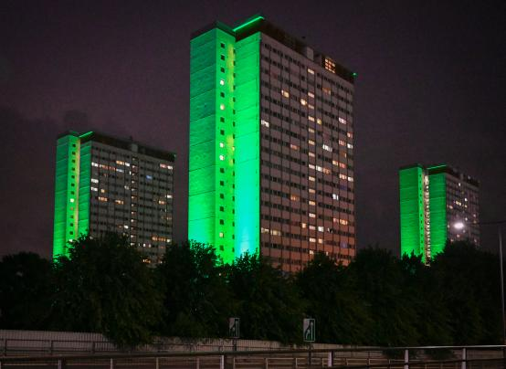 Towers at the Edward Woods Estate illuminated green in remembrance of the Grenfell Tower fire