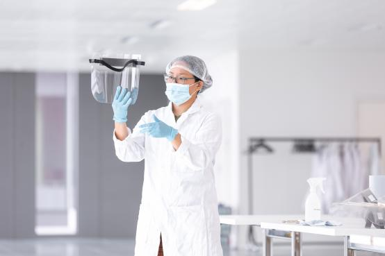 Woman in protective lab gear holding visor in the air