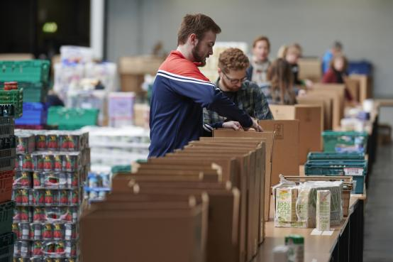 People working on packing food parcels inside one of Olympia London's large exhibition halls