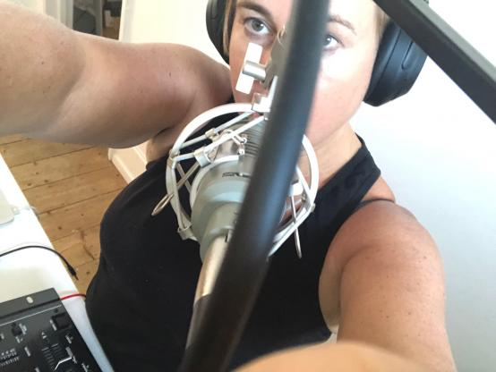 Jane McGrath speaking into a microphone while broadcasting on internet radio station Gaga Radio