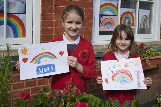 Brackenbury Primary School pupils holding their rainbow drawings