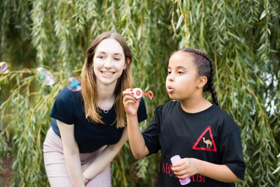 Young child with her helper standing in a garden blowing bubbles