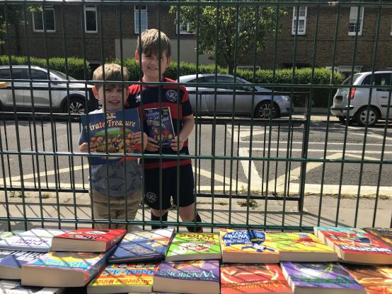 Two brothers from Old Oak primary school standing outside the school fence holding books