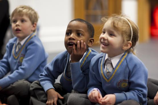School children sat in a group on the floor in their school uniform