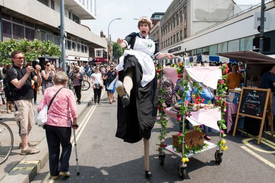 Tea lady on stilts at Hammersmith pop-up market