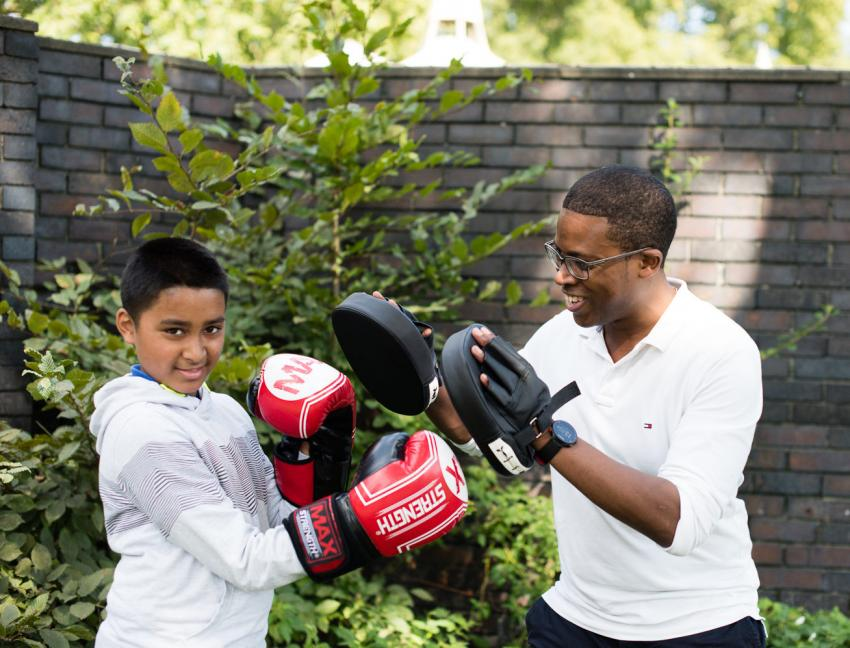 Young child and his helper boxing in a garden