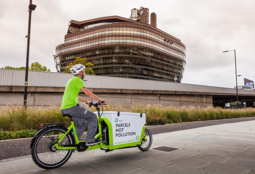 Electric cargo bike travelling on the road with The Ark building in the background
