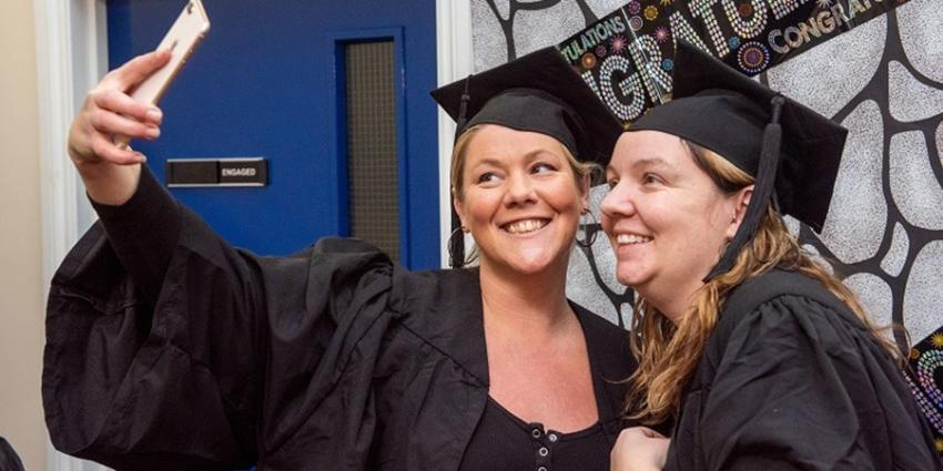 Two students wearing gowns and mortar boards taking a picture of themselves on a phone at graduation