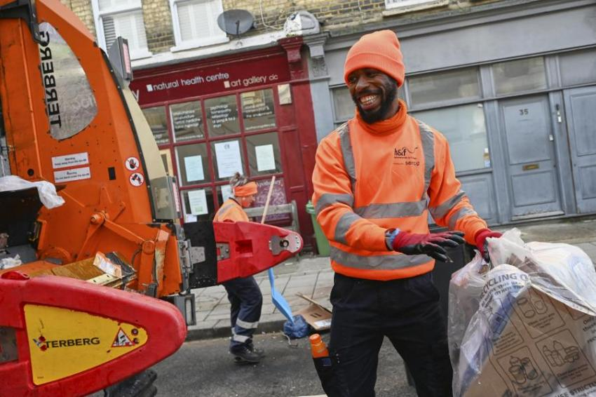 Cheerful bin man behind a recycling truck loading waste to be recycled