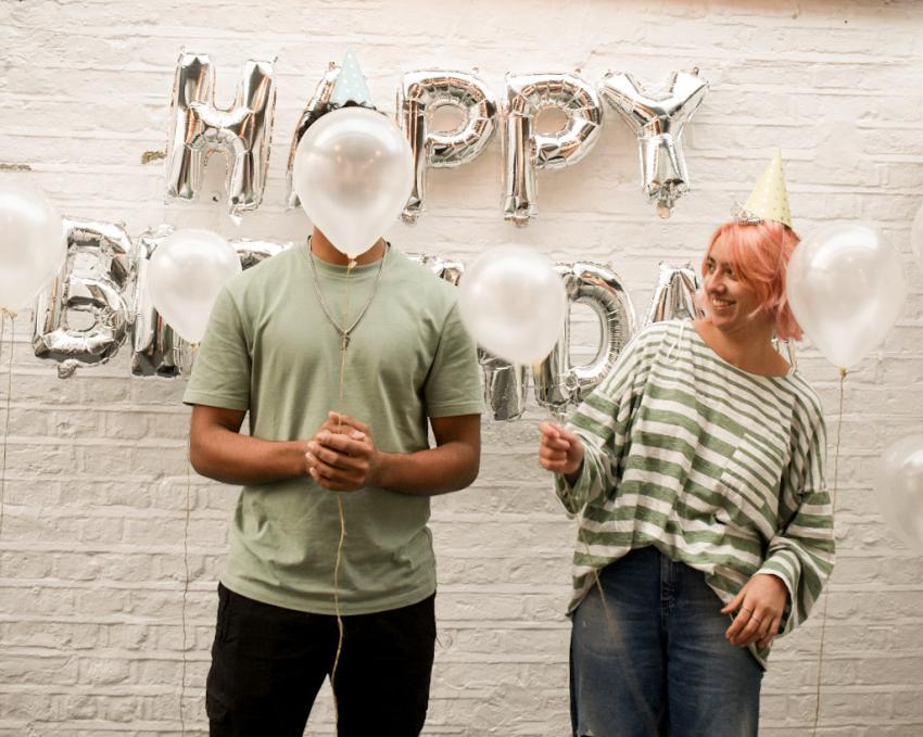 Rafey Asif and Mariana Sabio stood in front of a white brick wall holding first birthday balloons