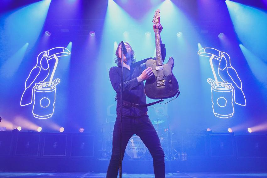 Catfish and the Bottlemen's lead guitarist standing on stage bathed in blue stage lighting