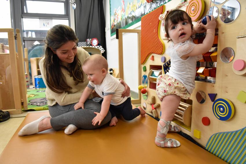 Adult woman and two young children using play equipment inside a play centre room