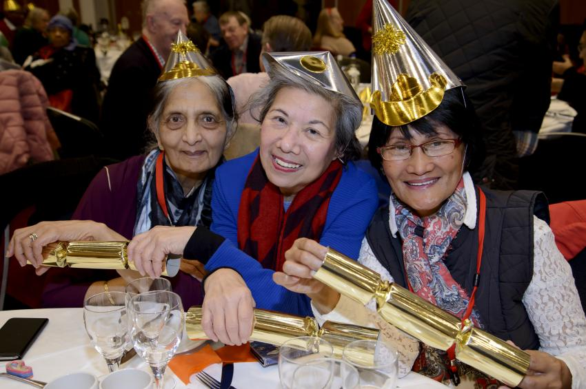 Three elderly women holding Christmas crackers sitting at a lunch table