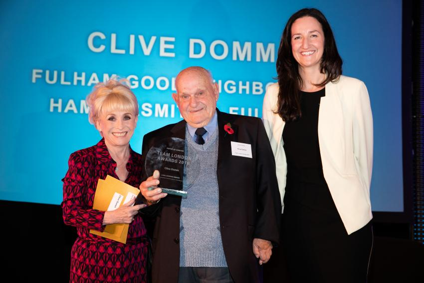 Clive Domm (centre) holding the Team London Award presented by Dame Barbara Windsor
