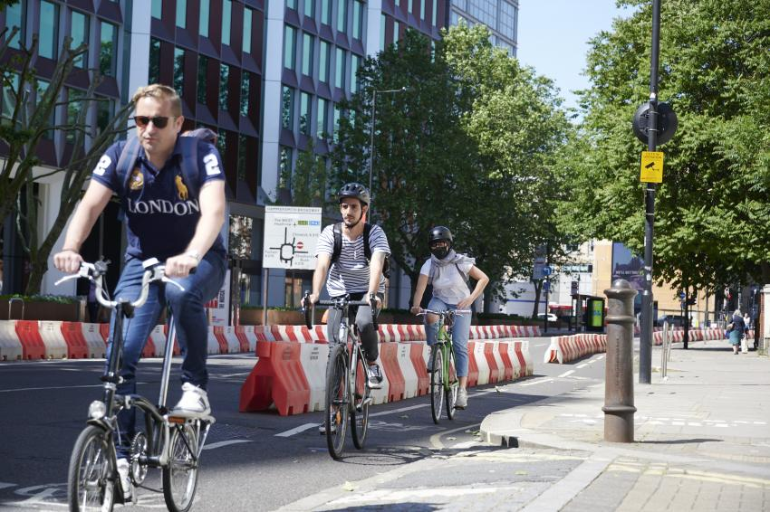 Cyclists riding along a street protected by temporary barriers