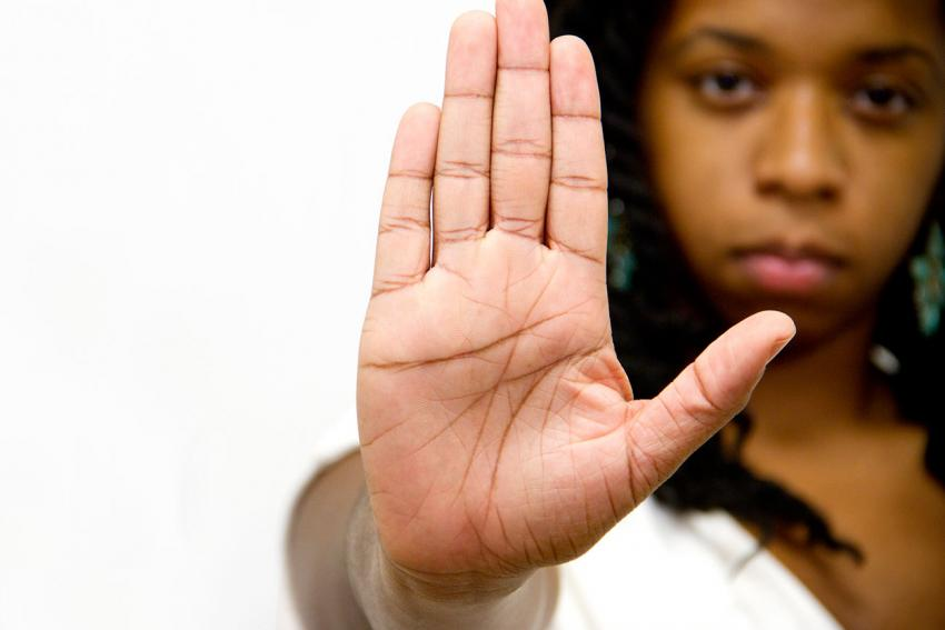 Woman's face with her hand raised palm forward