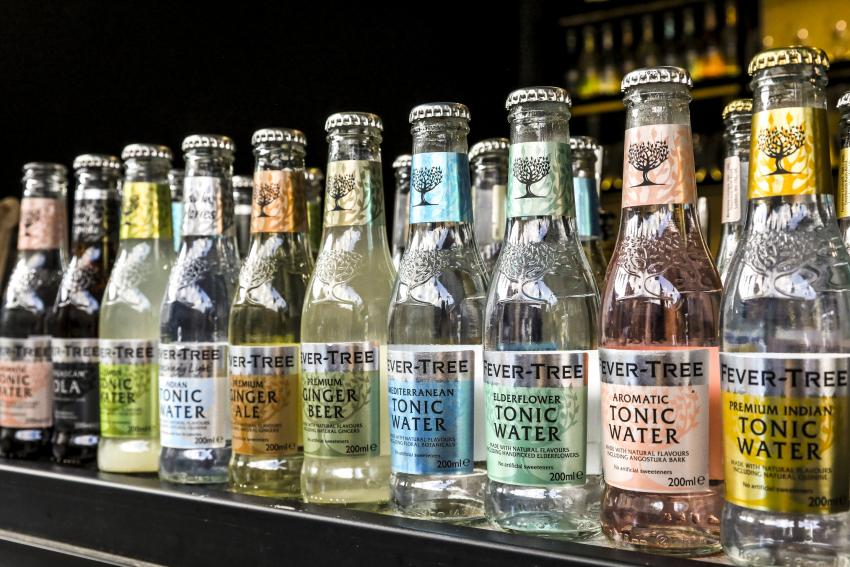 Bottles of Fever-Tree mixers in a row on a shelf in a bar