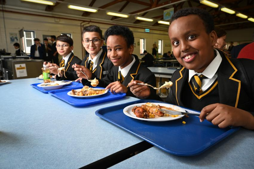 Four boys eating their school lunch from blue trays