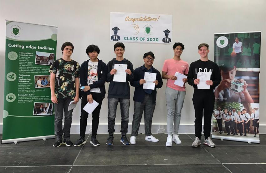 Group of male students stood on stage at Fulham Cross Academy picking up their GCSE results