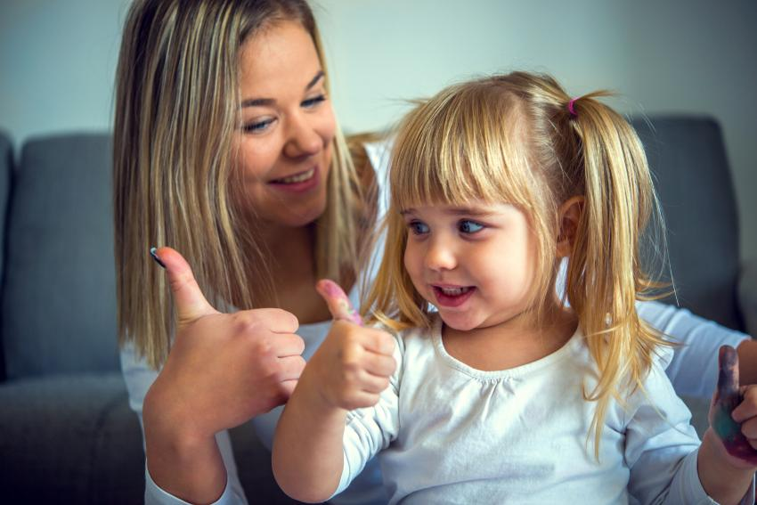 A mother and her child both putting their thumbs up