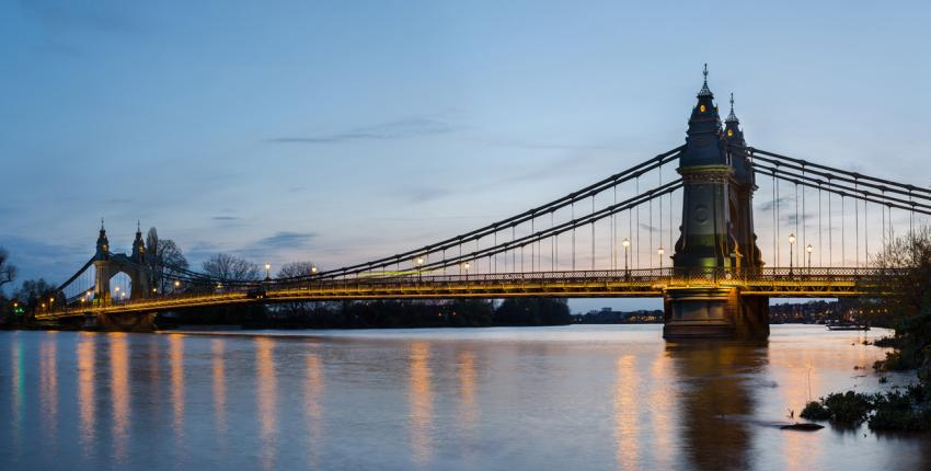 Hammersmith Bridge spanning the calm river Thames at dusk