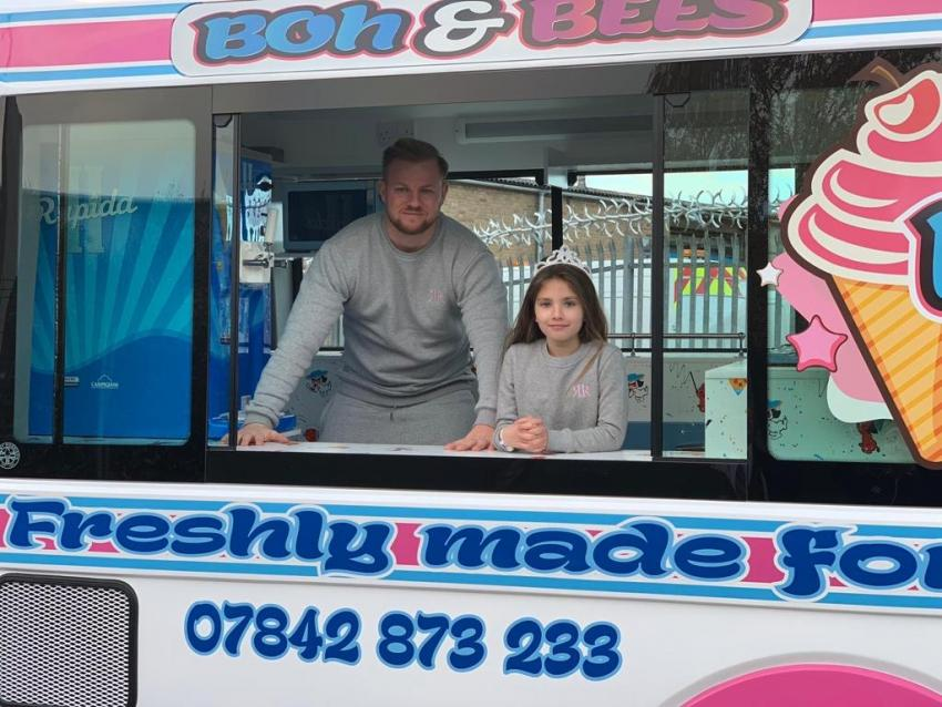 Jamie Hoult standing inside the window of his ice cream van with his daughter