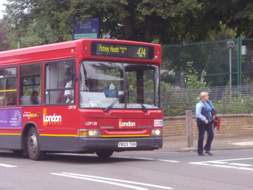 A 424 London bus driving along the road and a pedestrian walking alongside on the pavement