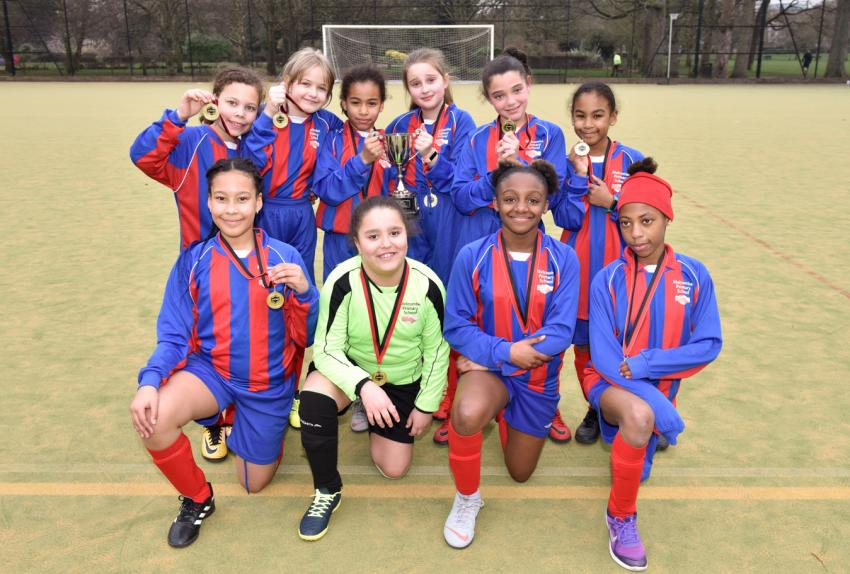 Team photo of the Melcombe primary football girls team with their 2019 Mayor's Cup trophy and medals