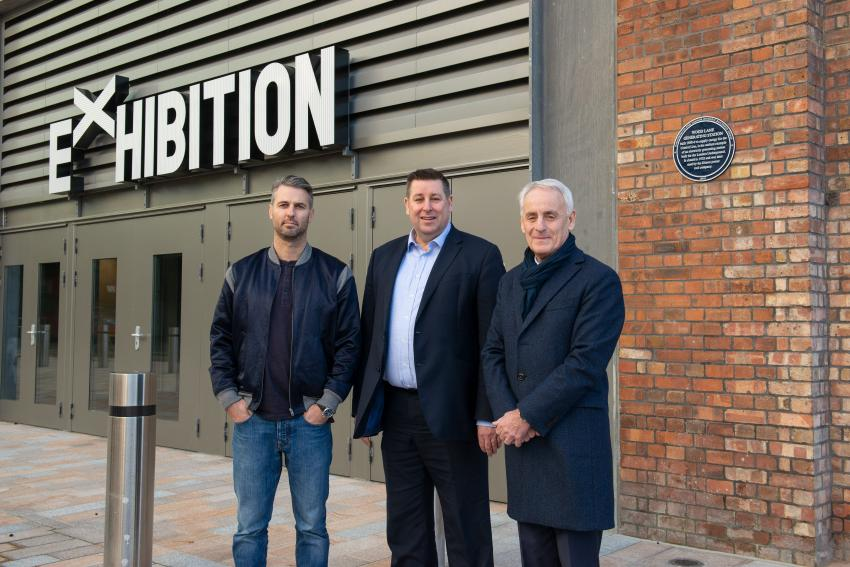 Dignitaries standing outside the Exhibition London venue underneath the new blue plaque