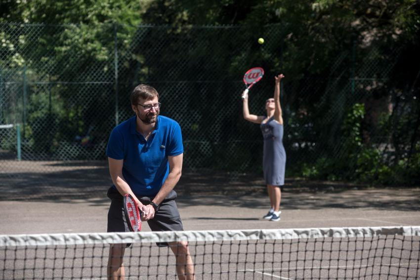 People playing tennis on a park court