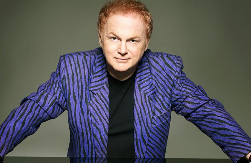 Mike Batt leaning on a table top