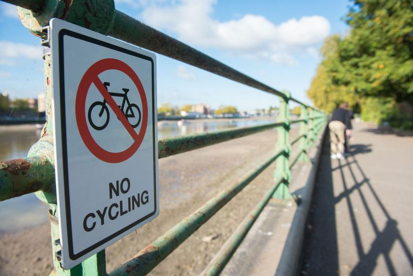 Railings separating the Thames and the Thames path next to Bishop's Park in Fulham showing a no cycling sign