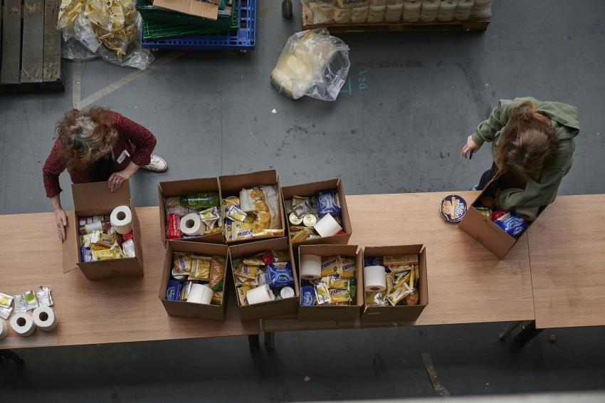 Food boxes on a table with two volunteers working alongside to get them packed
