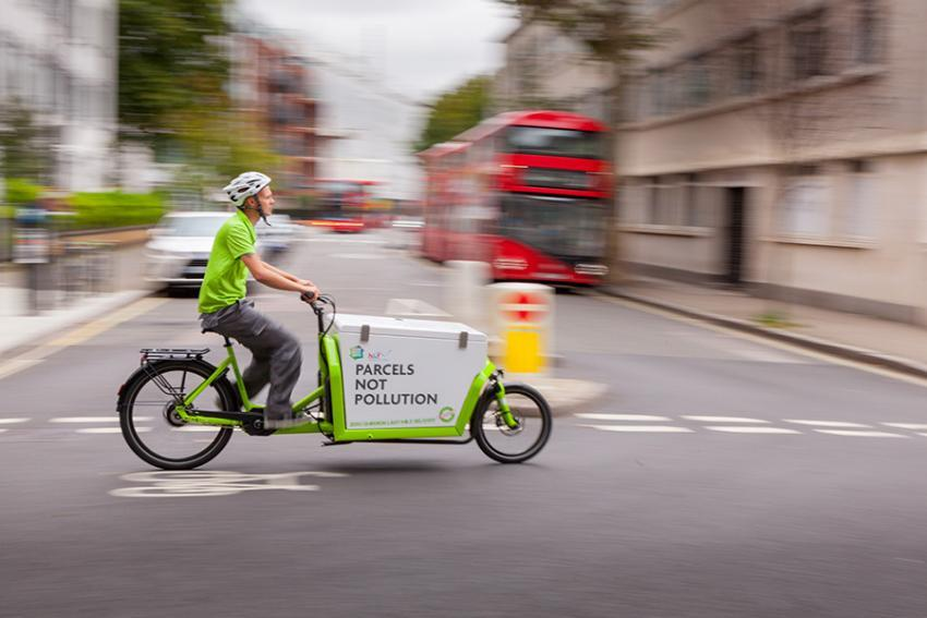Emission-free delivery cycle moving along the road surrounded by London buses