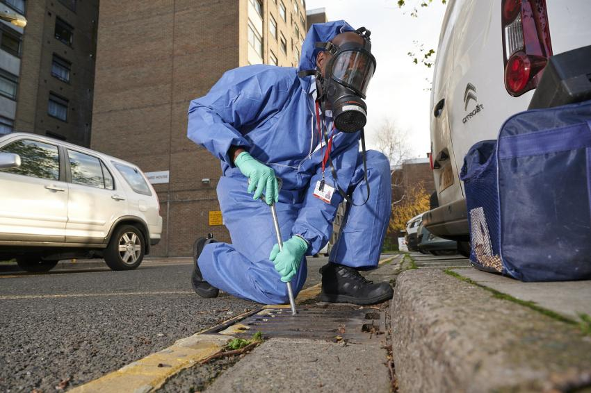 Pest control crew member kneeling at the roadside working on a drain