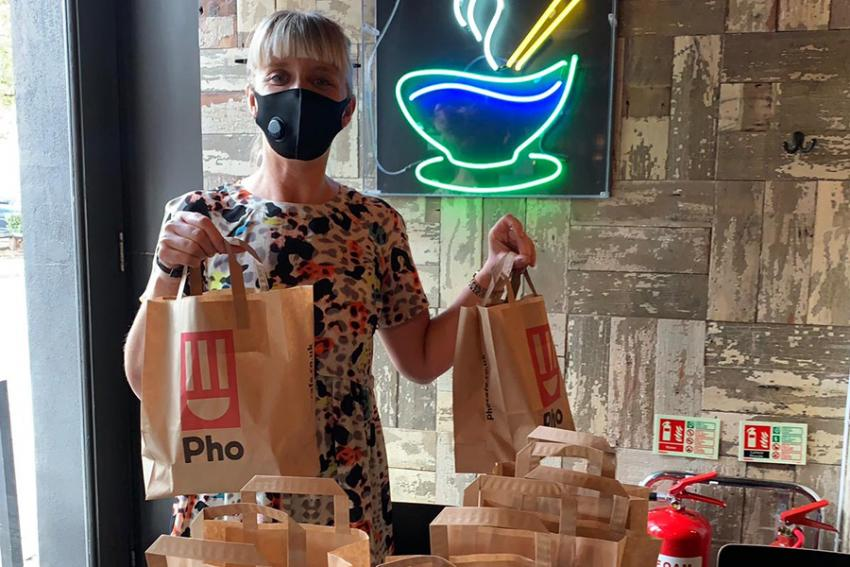 Woman holding 2 lunch bags provided by Vietnamese restaurant Pho