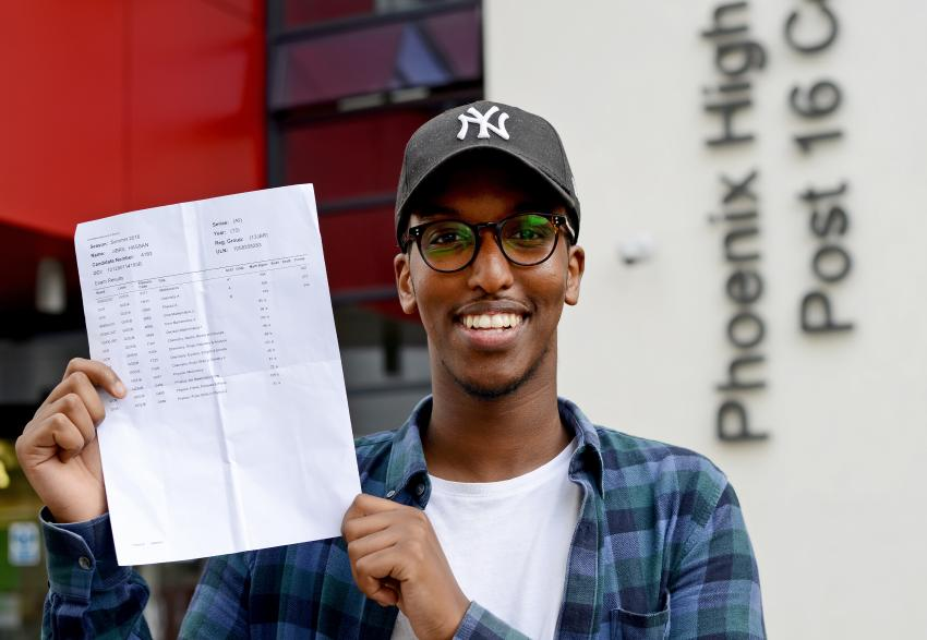 Students proudly hold up their results