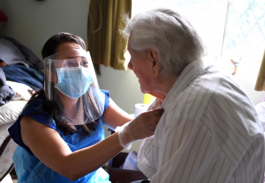 Careworker sitting on a bed in full PPE helping an elderly man sat next to her