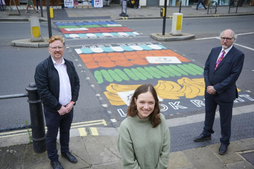 Artist, business improvement district manager and a councillor standing next to the rainbow crossing on North End Road