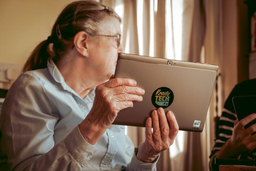 Elderly woman holding a reconditioned silver laptop in her hands