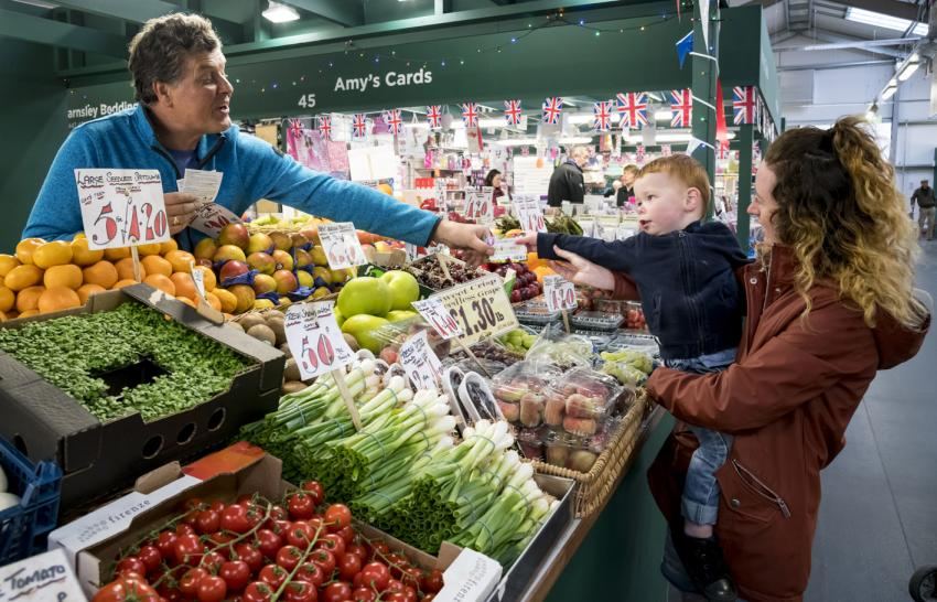 Child handing a voucher to fruit and veg seller