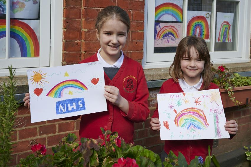 Two school children holding hand-painted NHS rainbows