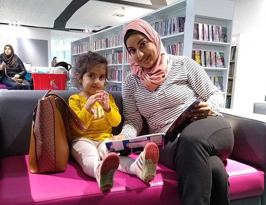 Woman and child sat on a bench in Shepherds Bush Library reading a book