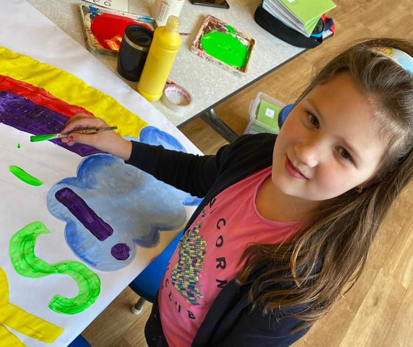 Child holding a paintbrush and painting a banner at a classroom table