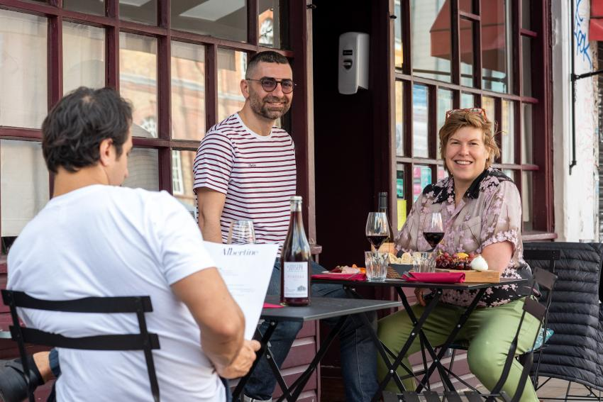 Residents sat outside a wine bar using tables and chairs on the pavement