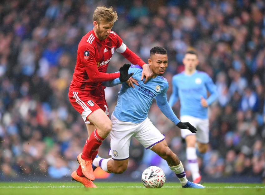 Tim Ream of Fulham on the pitch fouling opposition player Gabriel Jesus of Manchester City